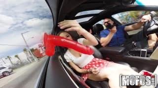 Brune chaude dans une voiture avec gode rouge